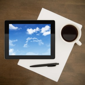 Digital tablet with clouds on screen lying on worktable with paper, pen and cup of coffee. Concept image on cloud-computing theme.